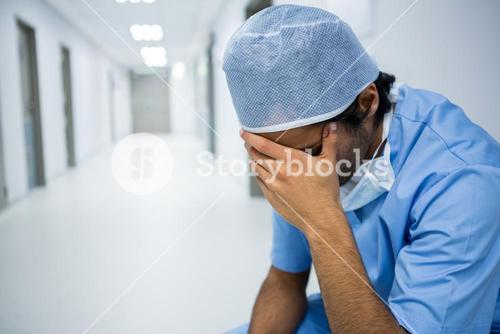 Tensed surgeon sitting with hand on forehead in corridor