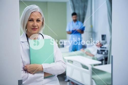 Portrait of female doctor leaning with file at the entrance of ward