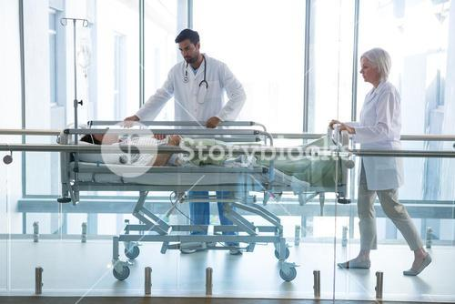 Doctor pushing emergency stretcher bed in corridor