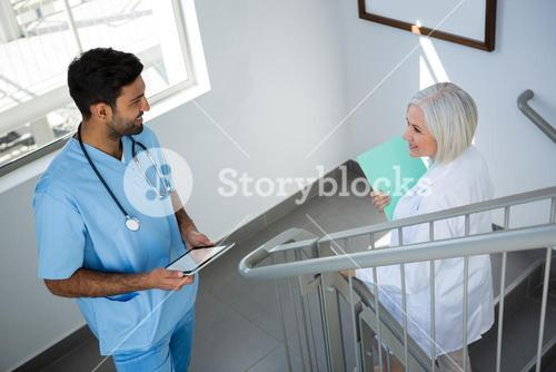 Doctors interacting while walking on stairs