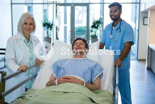 Portrait of doctors standing while patient lying on emergency stretcher