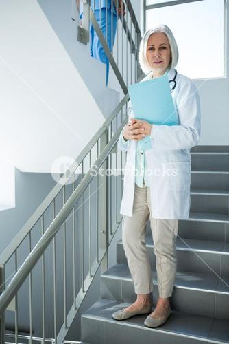 Doctor standing with file on staircase