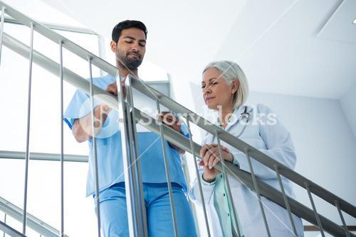Doctors discussing over digital tablet while standing on stairs
