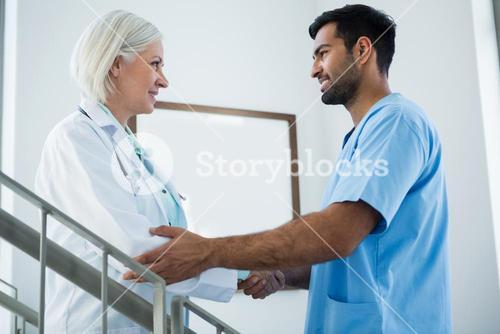 Doctors standing on staircase and shaking hands
