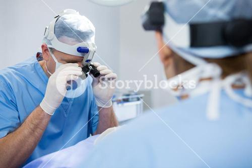 Surgeons wearing surgical loupes while operating patient