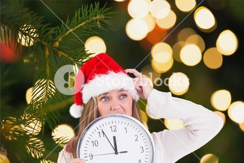 Thoughtful woman in santa hat holding a clock
