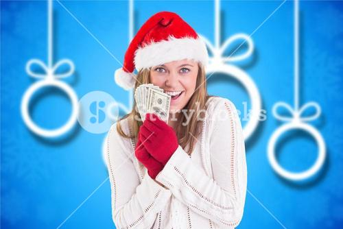 Beautiful woman in santa hat holding currency note