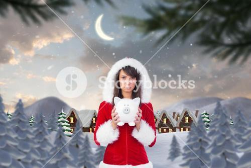 Sad woman in santa hat holding piggybank