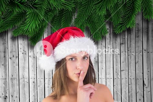 Portrait of beautiful woman in santa hat with finger on lips
