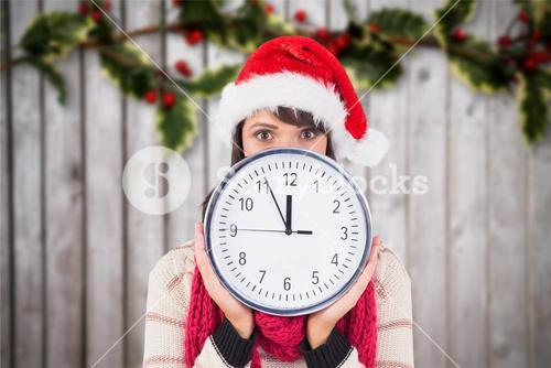 Woman in santa hat holding a wall clock against digitally generated background