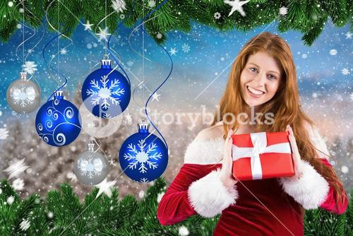 Beautiful woman in santa hat showing a christmas gifts
