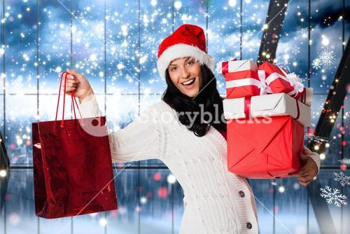 Beautiful woman in santa hat holding a christmas gift and shopping bag