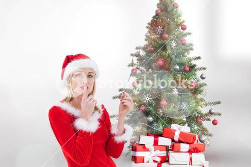 Female santa with finger on lips standing near gifts and christmas tree