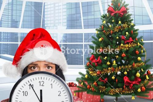Woman in santa hat hiding behind a clock