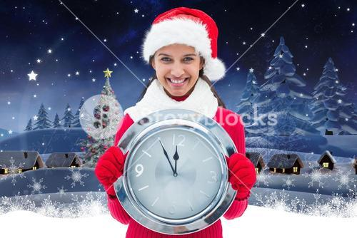 Happy woman in santa hat holding a wall clock