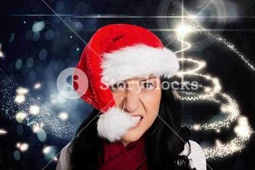 Frustrated woman biting santa hat
