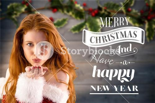 Beautiful woman in santa costume blowing a kiss with christmas greetings