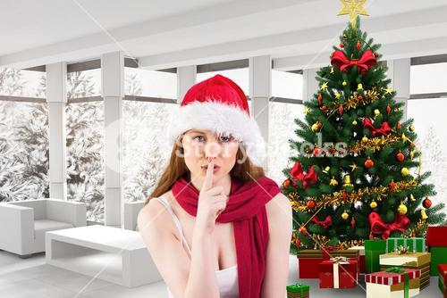 Woman in santa hat with finger on lips