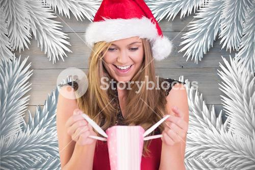 Excited woman in santa hat looking at christmas gift
