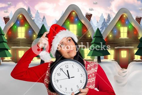 Thoughtful woman in santa hat holding clock
