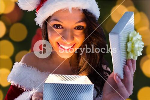 Excited woman in santa costume opening christmas gift