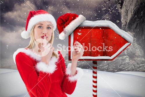 Female santa with finger on lips standing in snowfall