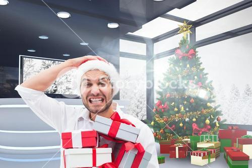 Frustrated man in santa hat holding gift boxes