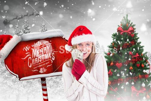 Excited woman in santa hat holding currency notes