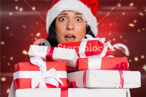 Shocked woman in santa hat holding stack of gift boxes