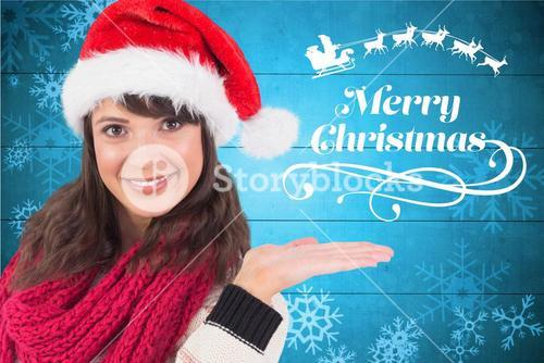 Beautiful woman in santa hat gesturing against digitally generated background