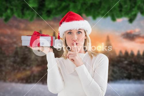 Beautiful woman in santa hat holding a gift box with finger on lips