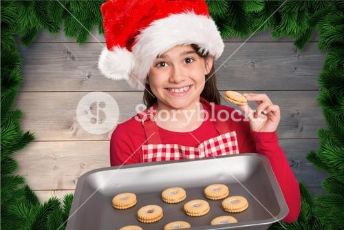 Girl in santa hat holding a tray with freshly baked biscuits