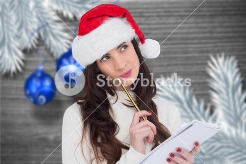 Thoughtful woman in santa hat making a wish list