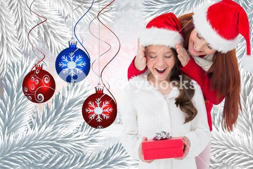 Mother presenting daughter with a surprise christmas gift