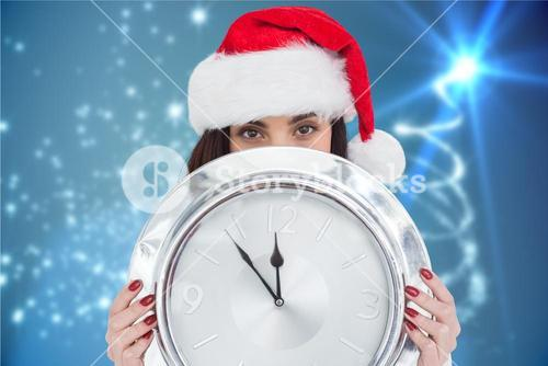 Beautiful woman in santa hat holding wall clock