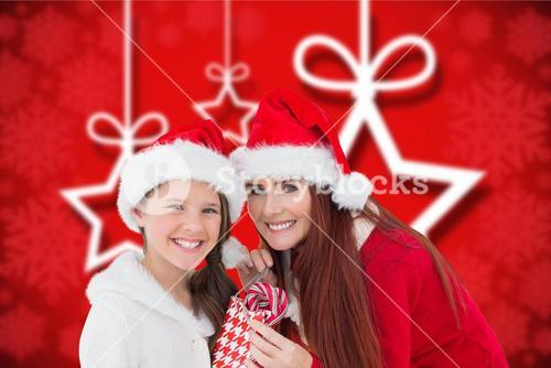Mother and daughter in santa hat holding a bag of candy cane