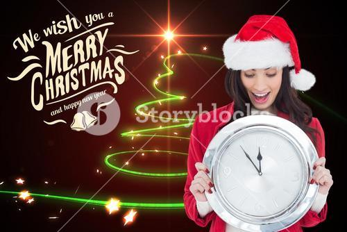 Beautiful woman in santa costume holding wall clock during christmas time