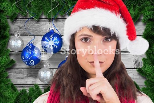 Beautiful woman in santa hat with finger on lips