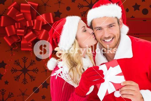Woman kissing man on cheeks against digitally generated background