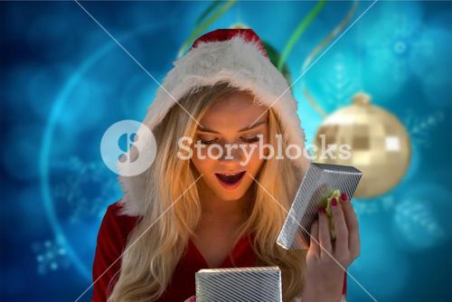 Surprised woman in santa hat looking at christmas gifts