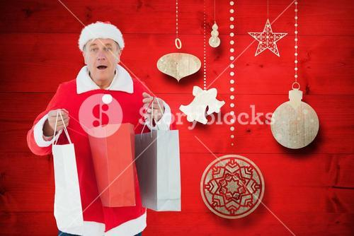 Man in santa costume holding shopping bags against digitally generated background