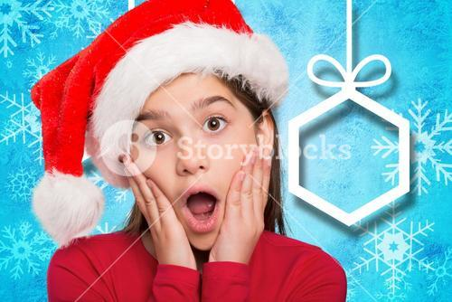Surprised girl in santa hat against digitally generated background