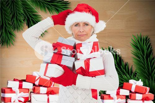 Confused woman in santa hat holding christmas gift