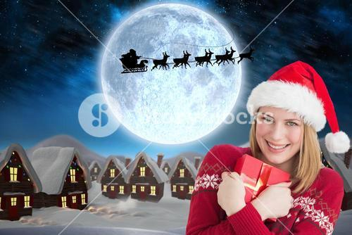 Beautiful woman in santa hat holding christmas gift