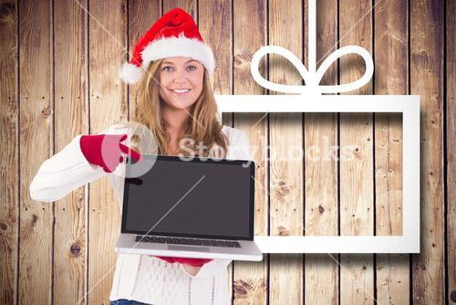 Pretty woman in santa hat and gloves pointing at laptop