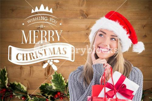 Thoughtful woman holding christmas gifts and smiling