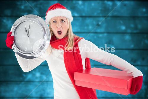 Anxious woman in santa hat holding a clock and christmas gift