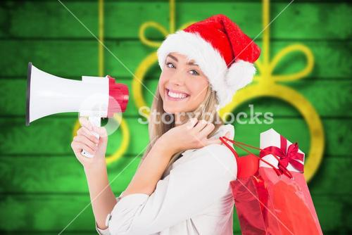 Smiling woman in santa hat holding christmas gifts and megaphone