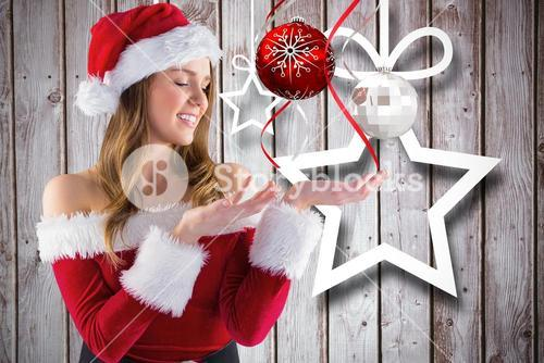 Beautiful woman in santa costume pretending to hold a imaginary christmas decoration
