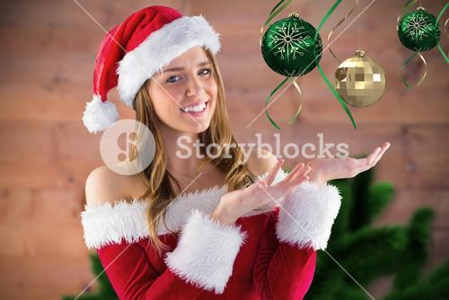 Smiling girl pretending to hold a imaginary christmas decoration